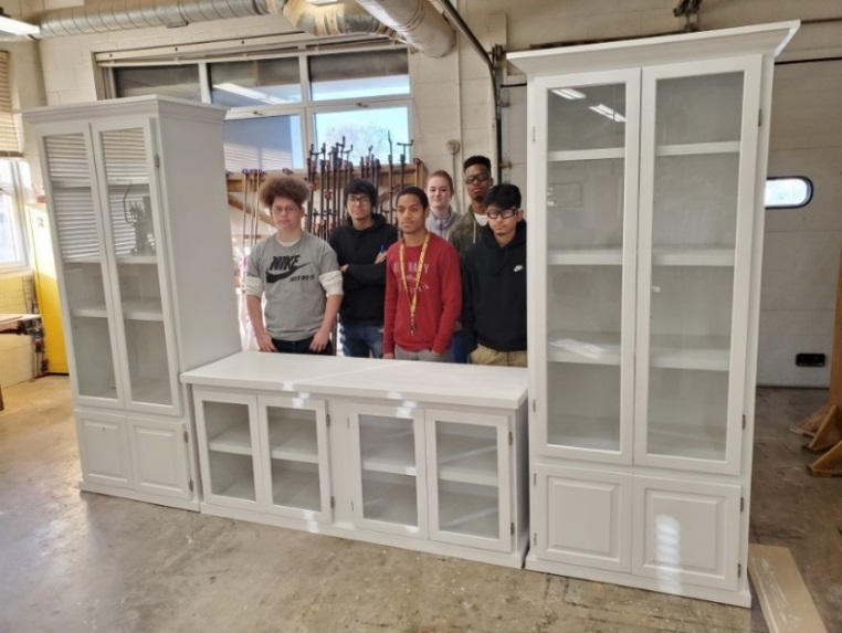 Students pose with an entertainment center created in Mr. Hatfield's construction trades class.