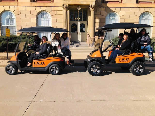 Main Building Admins and the Gossrow family posing with the donated golf carts.