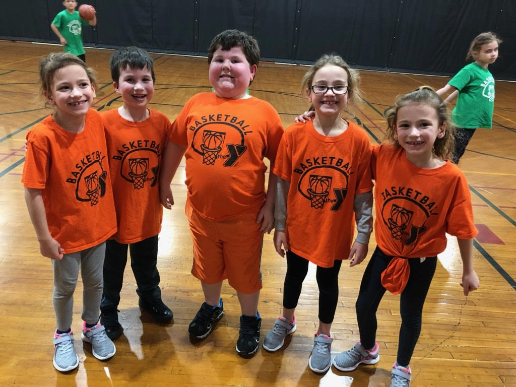 ISD Elementary YMCA basketball team posing together for a picture on the basketball court. .